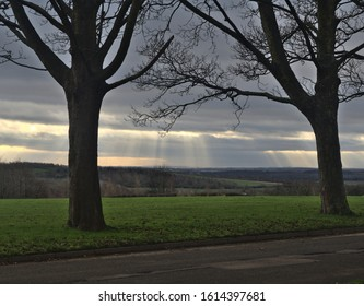 Leeds, West Yorkshire, England, Britain, January 2020, sun rays shining on landscape through clouds between two trees