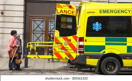 LEEDS,UK - 6 AUGUST 2015.  Picture of people onlookers looking worried into the back on an emergency ambulance
