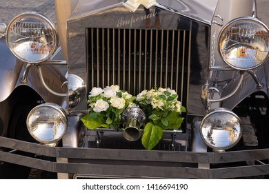 Leeds,West Yorkshire,United Kingdom.10.27.2018.The front of a silver Imperial Launderlette Wedding Car decorated with bunches of white Roses.