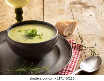 leek cream soup in a dark bowl on a plate, wine, bread and spoon on a rustic wooden table, copy space, selected focus, narrow depth of field