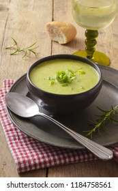 leek cream soup in a dark bowl on a plate, wine, bread and spoon on a rustic wooden table, vertical, selected focus, narrow depth of field