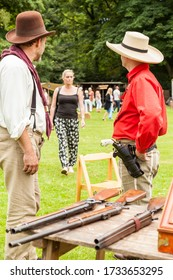 Leek, Staffordshire, England. - June 21st 2014:Two Men in American cowboy costume part of a western weekend with  the lone star old west re-enactment group looking at attractive woman approaching them