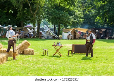 Leek, Staffordshire, England. - June 22nd 2014: Bandit with pistol drawn attacking man with a lasso rope as part of an American western scene played out by the lone star old west re-enactment group.