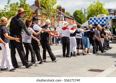 Leek, Staffordshire, England, U.K - June, 21 2014 : People of all ages line dancing in the street as part of Leek's Country and Western weekend. Leek, Staffordshire, England.