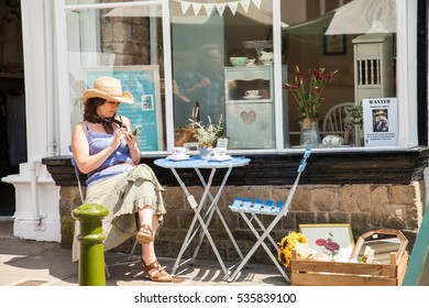 Leek, Staffordshire Moorlands, England, U.K - June 21 2014 : Young woman wearing straw cowboy hat sitting outside a shop window text messaging at the Leek  Country and Western weekend, England.