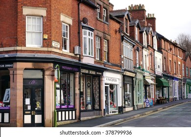 LEEK, UK - DECEMBER 31 2015: A row of small, independent shops occupies the ground floor of historic red brick terraced houses in Leek, a historic market town in the Staffordshire Moorlands, England.