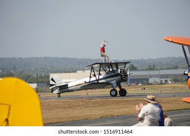 Leesburg, VA / USA - September 28, 2019: A stunt man stands on top of a plane at the Leesburg Air Show.