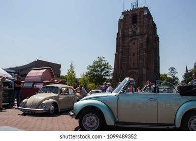 Leeuwarden, Friesland - May 26th 2018: Men pushing a VW Beetle to jumpstart it during an exhibition of VW at the square near the Oldehove.