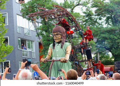 LEEUWARDEN, NETHERLANDS - August 18, 2018. People are taking pictures of the gigantic female marionette puppet of Royal de Luxe street theater in urban city street of Cultural Capital of Europe.