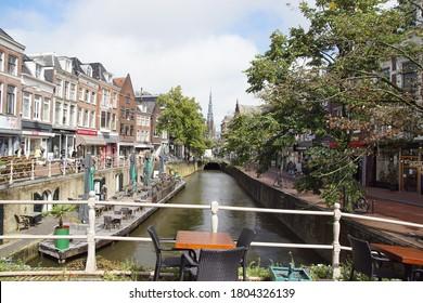 Leeuwarden, Netherlands, August 26, 2020. Canal, bridge, boat, street, shops with the Sint-Bonifatiuskerk church in the background in Leeuwarden, Friesland, Netherlands.