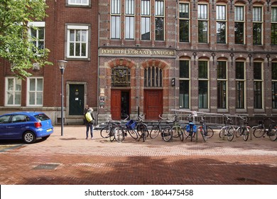 Leeuwarden, Netherlands, August 26, 2020. Old Dutch post office and telegraph office in the city of Leeuwarden. Now hotel Post Plaza. With bicycles and people in the street.