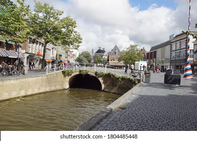 Leeuwarden, Netherlands, August 26, 2020. Canal with a bridge. On the bridge a square with the historic building De Waag, shops and people in Leeuwarden, Friesland, Netherlands.