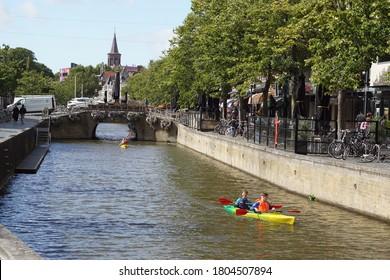 Leeuwarden, Netherlands, August 26, 2020. Canal, bridge, terraces, street, shops, houses in Leeuwarden, Friesland, Netherlands. People in lifejackets sail by canoe along the canal.