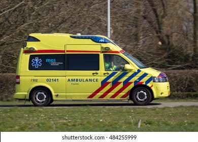 LEEUWARDEN, THE NETHERLANDS - Dutch ambulance Volkswagen Transport speeding on the road.