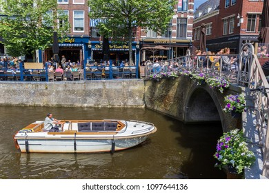 LEEUWARDEN, NETHERLANDS - MAY 20, 2018: Small boat going under a bridge in Leeuwarden, Netherlands