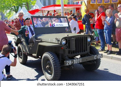 LEEUWARDEN, NETHERLANDS - May 5, 2018. Elderly Canadian war veteran Jim Parks drives in oldtimer military jeep while audience is applauding on Bevrijdingsdag (Liberation Day). End of war celebrations.