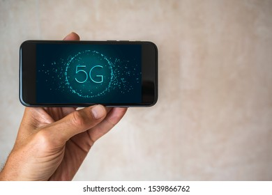 lef hand holds black mobile phone with modern technoligie G5 network graphic on display modern look warm colored blurred background copy space