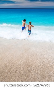 LEFKADA, GREECE - CIRCA AUGUST 2015 - Two boys playfully running into the sea at Kathisma beach, one of many beaches  on Greek Lefkada island.