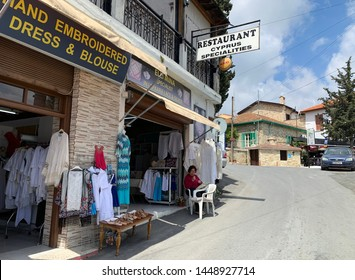 LEFKARA, CYPRUS - MAY 10, 2019: Craftswoman embroiders lace on the threshold of her shop in the historical village of Lefkara