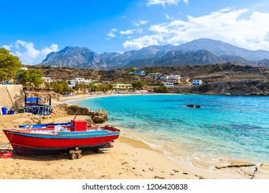 LEFKOS PORT, KARPATHOS ISLAND - SEP 29, 2018: Fisherman repairing boats on beautiful beach in Lefkos village on coast of Karpathos island, Greece.