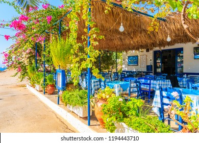LEFKOS VILLAGE, KARPATHOS ISLAND - OCT 1, 2018: Terrace with tables in traditional Greek tavern decorated with flowers in Lefkos village on Karpathos island, Greece.