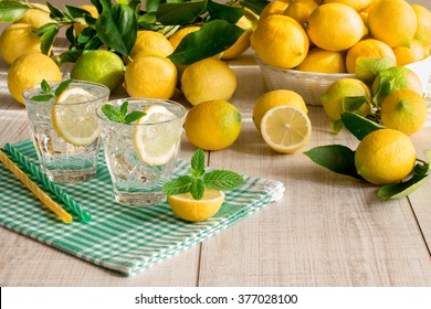 Left 2 glasses of soda water with a slice of lemon, mint leaves, ice cubes on green checkered napkin behind lemons scattered and in a basket on a light wood background. Lemon soda water. Horizontal.