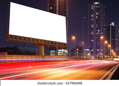 Left blank billboard on light trails, street and urban in the night - can advertisement for display or montage product or business.