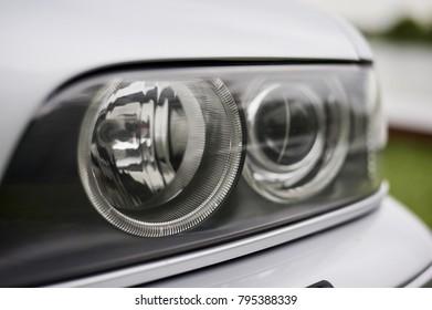 Left car headlight on a car of gray
