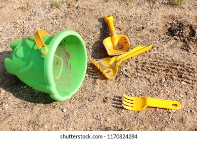 Left children toys on the sand. Green bucket and yellow tools. Child abuse.
