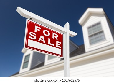 Left Facing For Sale Real Estate Sign In Front of House and Deep Blue Sky.