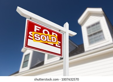 Left Facing Sold For Sale Real Estate Sign In Front of House and Deep Blue Sky.