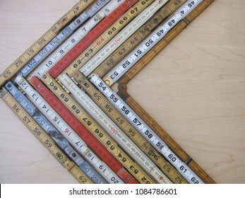 Left facing vector or chevron graph made of folding rulers in metric and inches representing accuracy, measurement, decrease or downturn with copy space.
