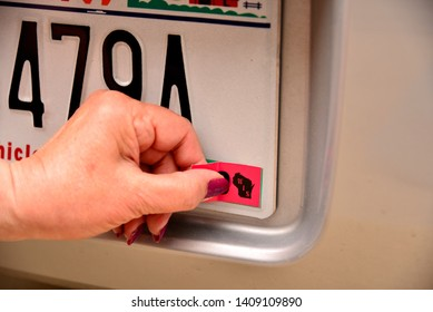 Left female hand applying registration sticker with thumb and forefinger to be in compliance for annual state requirements.