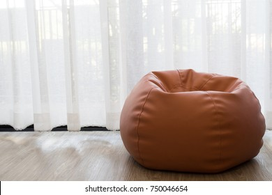 Left free space with Bean bag with white curtain window in living room.