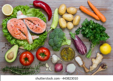 Left fresh salmon fillets on the lettuce near summer season vegetables, herb, spices and olive on wood background. Salmon fillets and summer vegetable ingredients, spices. Horizontal. Top view.