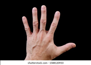 Left hand, adult male, facing downwards, showing back of hand, isolated on black background. Asian man's hand, fingers spread, palm down, dorsal view, lying on black surface. Closeup, top view.