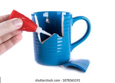 Left hand applying glue to a broken ceramc coffee cup