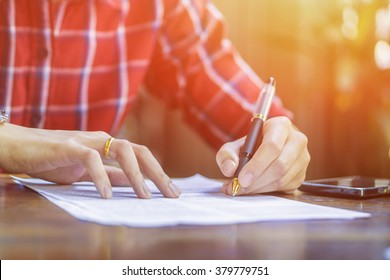 left hand Businessperson Signing Contract, man writing with pen and reading books at table,Form. in office,vintage tone ,morning light ,selective focus.