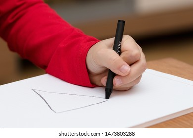 Left hand of a child drawing on white paper using black crayon