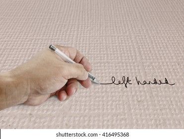 A left hand holding a ball point pen writing the word Left Handed on a grungy paper.
