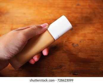 Left hand holding beige BB concealer foundation makeup cosmetic cream transparent bottle with white cap, with shadow, on red brown wooden texture table top background