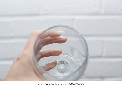 Left hand holding an empty glass. Perspective is first person point of view drinking from the cup with whitewash brick background.