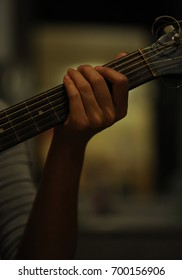 left hand holding a guitar, hold guitar on black background, start playing guitar with basic level