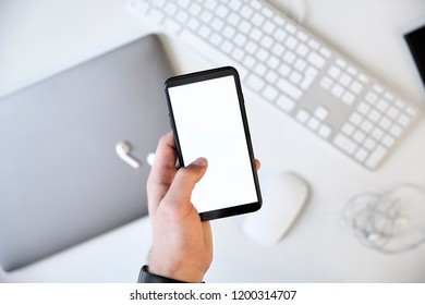 Left hand holding a mobile phone with white screen over the white desk.