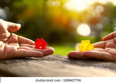 Left hand holding red and yellow model car holding.Have a solar background. Home loan with car exchange or trade in business or real estate.For family happiness.