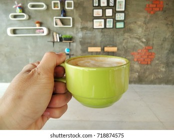 The left hand holds a hot coffee.