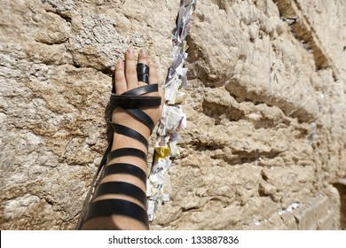 The left hand of a Jewish adult (early 30's) Caucasian man wrapped with Phylacteries, resting on the holy Western Wall (aka Wailing Wall) in the old city of Jerusalem, Israel.
