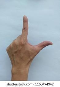 """Left Hand, L-sign overhand, """"Loser"""" symbol. Asian male hand model."""