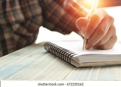 Left hand of people, student writing and note on notebook on wood table with copy space, in library, concept as education attempt and make effort to win, intend to improve knowledge for future life