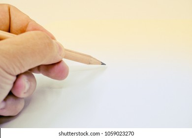 Left hand writing with pencil on the empty page
